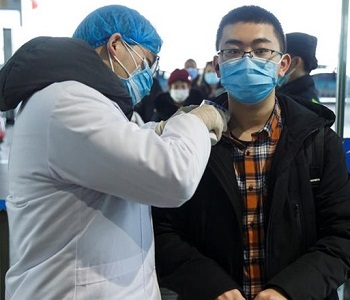 man wearing masks is screened by gowned health worker for COVID-19